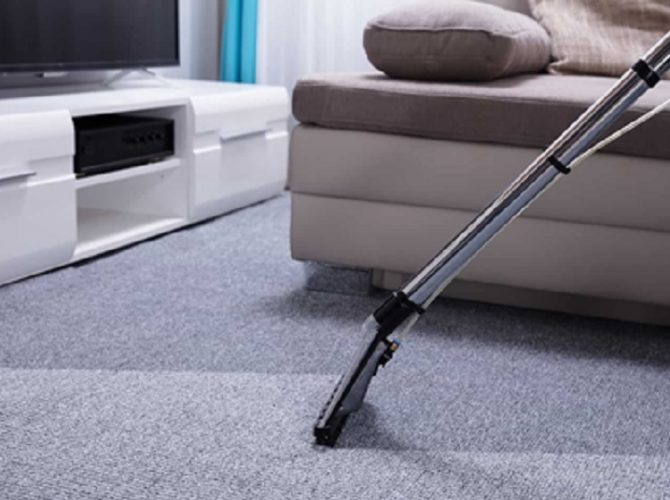 steam cleaner cleaning home carpet with grey couch and tv on white sideboard in background